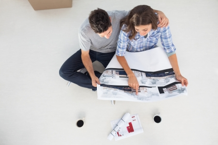 Overview of a husband and his wife looking at house plans sitting in their new house photo