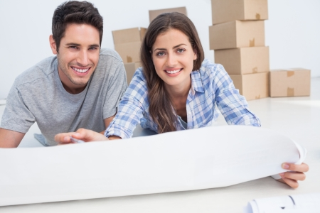 Portrait of a couple lying on the floor and holding a house plan in their new house photo