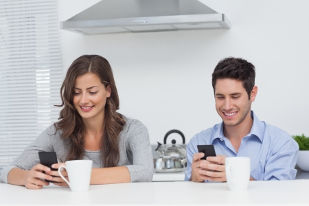 Couple using their smartphones in the kitchen photo