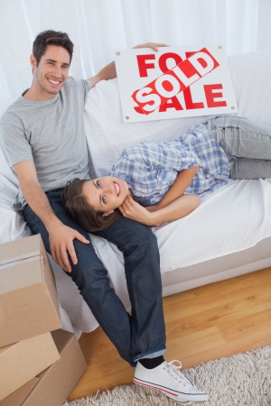 Man in his new house holding a sign with sold written on it with his wife lying on him photo