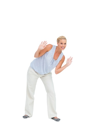 bending down: Blonde woman bending down with hands up on white background