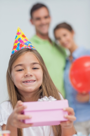 Little girl holding a birthday present during her birthday photo