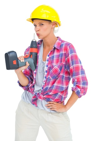Serious handy woman with a power drill on white background photo