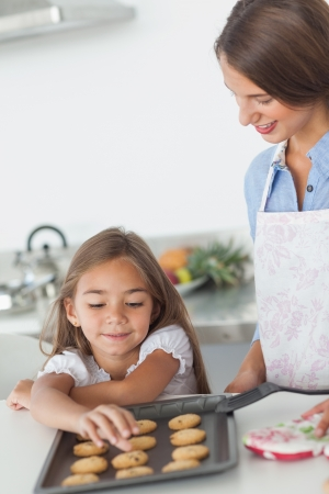 Little girl grabbing a cookie from a baking pan in the kitchen photo