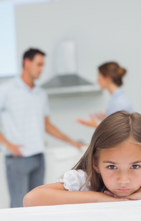 Little girl being sad while parents are quarreling in the kitchen photo