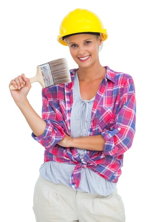 Attractive handy woman holding a brush and smiling at camera on white background  photo