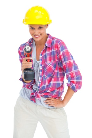 Smiling handy woman with a power drill on white background photo