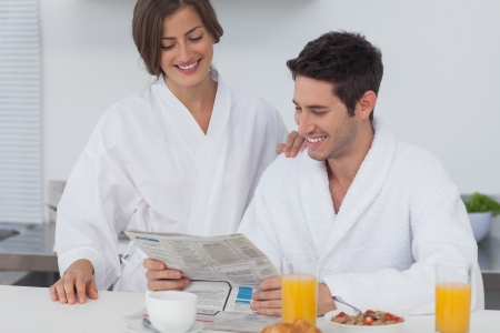Man reading a newspaper while having breakfast with his wife photo