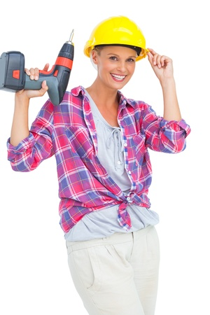 Smiling handy woman holding a power drill on white background  photo