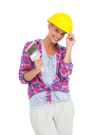 Handy woman touching her helmet and holding paintbrush on white background  photo