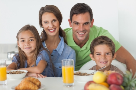 Portrait of parents having breakfast with their children in the kitchen Stock Photo - 20639256