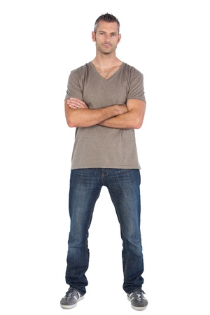 assertive: Focused man with arms crossed on a white background