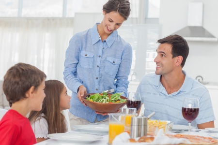Pretty woman bringing a salad to her family for the dinner Stock Photo - 20668351