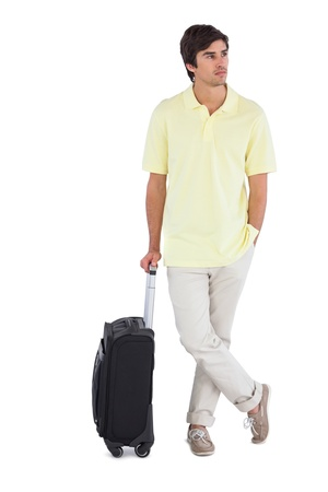 chinos: Serious man standing with his suitcase on q white background Stock Photo