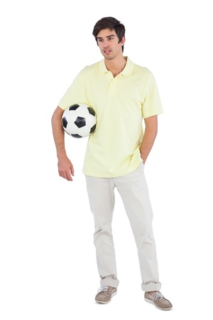 chinos: Serious man holding soccer ball on a white background