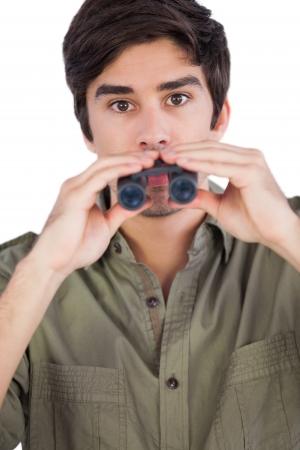 envisioning: Man holding binoculars and looking at the camera