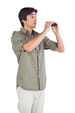 envisioning: Surprised man holding binoculars on a white background