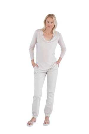 Smiling woman with hands in pockets on a white background photo