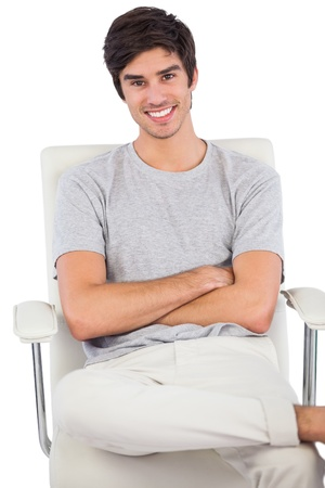 chinos: Smiling man with arms crossed sitting on a swivel chair on a white background Stock Photo