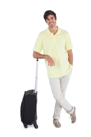 chinos: Smiling man standing with his suitcase on a white background