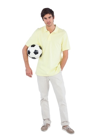 chinos: Young man holding soccer ball on a white background