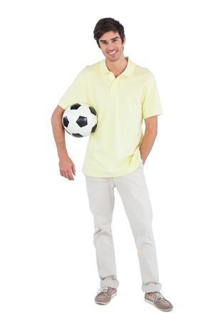chinos: Smiling  man holding soccer ball on a white background