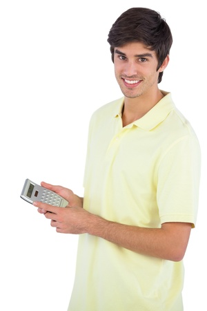 figuring: Smiling man using calculator on a white background