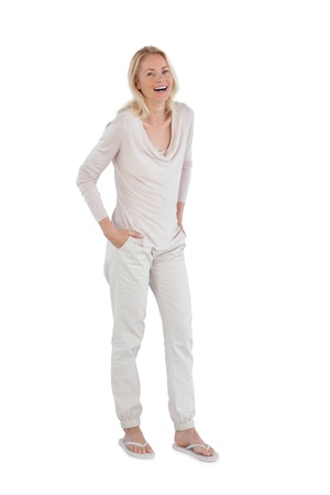 Laughing woman with hands in pockets on a white background photo
