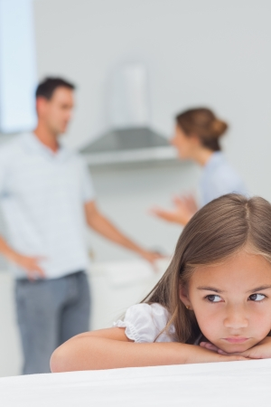 Upset little girl listening to parents who are arguing in the kitchen photo