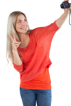Woman making peace sign while taking a picture of herself on a white background photo