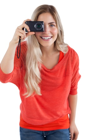 Blonde woman holding digital camera on a white background photo