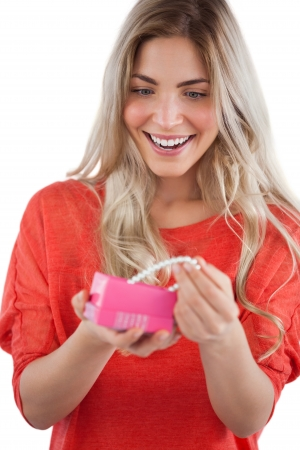 Blonde woman discovering pearl necklace in a gift box photo