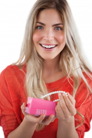 Cheerful woman discovering pearl necklace in a gift box photo