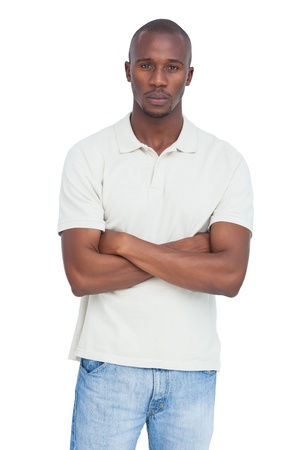 unsmiling: Unsmiling man with arms crossed on a white background