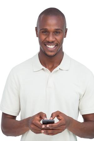 Lachende man met zijn mobiele telefoon op een witte achtergrond Stockfoto