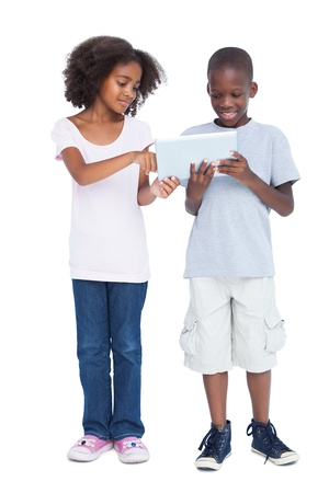 Brother and sister using tablet pc on a white background photo