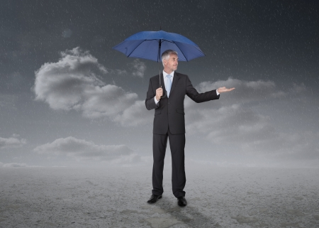 Businessman holding a blue umbrella  during a stormy weather photo
