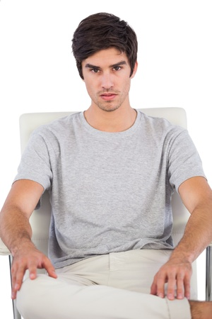chinos: Serious man sitting on a office chair on a white background