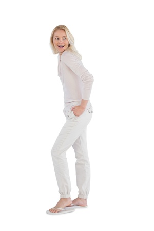 Happy woman with hands in pockets on a white background photo