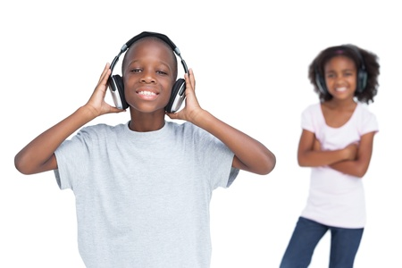 Brother and sister using headphones to listen to music photo