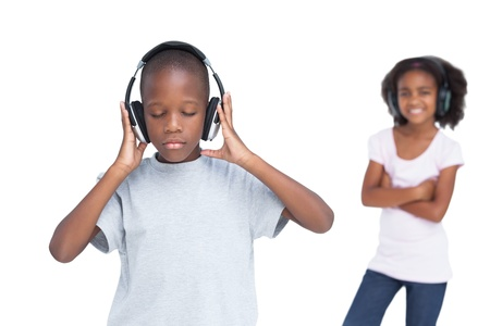 Little boy with eyes closed listening to music with his sister on a white background photo