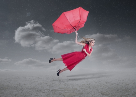 Attractive woman flying with a broken umbrella during a stormy weather photo