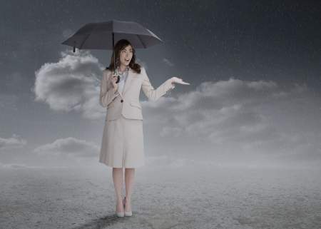 Businesswoman holding an umbrella during a stormy weather photo