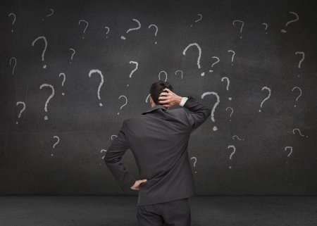 hesitating: Rear view of a doubtful businessman looking at various question marks drawn on a grey wall