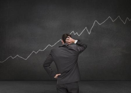 hesitating: Hesitating businessman looking at white chart drawn on a black board