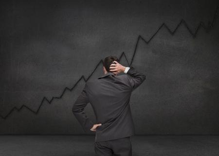 dudando: Dudando de negocios mirando gr�fico negro dibujado en un tablero negro