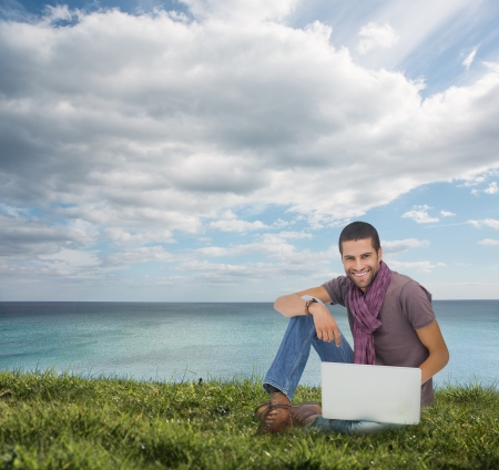 Handsome man sitting on the grass using his laptop photo