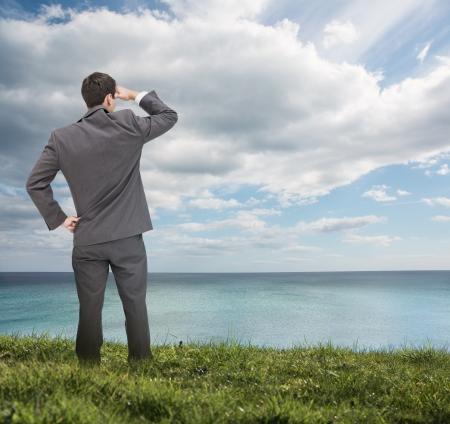 leuchtend: Stilvolle Geschäftsmann, der auf dem Gras und Blick auf das Meer