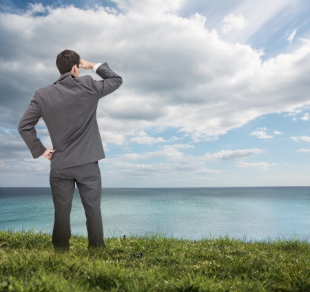 bright future: Stylish businessman standing on the grass and looking at the sea