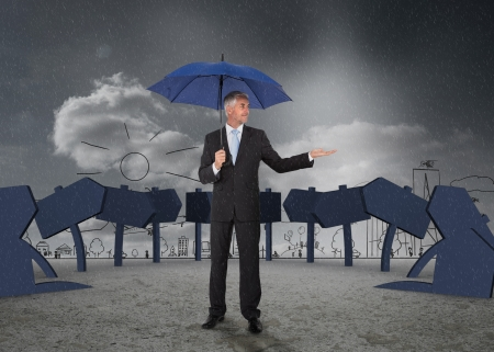 Businessman showing signs and a city and holding blue umbrella photo